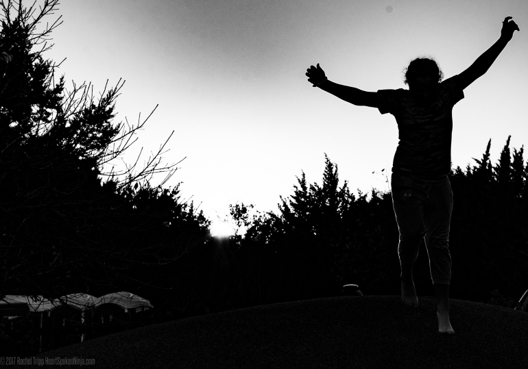 Professional Black and White Photography. Child jumping at park at sunset.